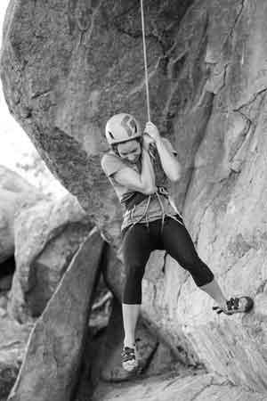 klatrende kvinne henger i tau
